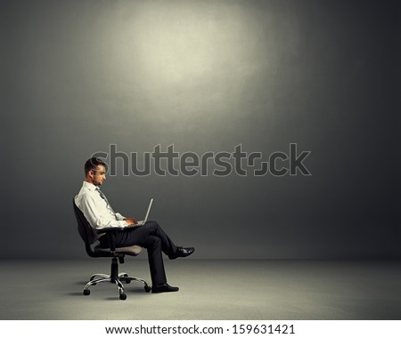 concentrated young businessman sitting in empty dark room and working with laptop - stock photo