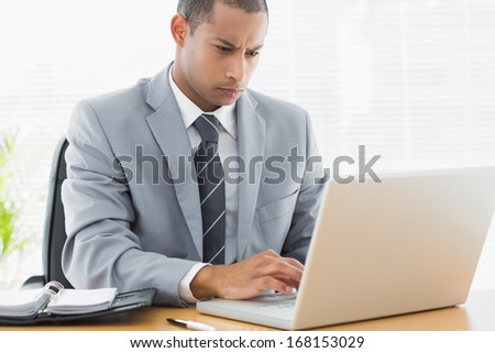 Concentrated young businessman using the laptop at office desk