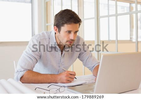 Concentrated young businessman working on blueprints and laptop in the office