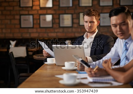 Concentrated young businessman working on laptop in restaurant
