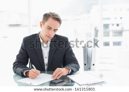 Concentrated young businessman writing documents at office desk - stock photo