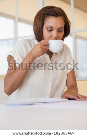 Concentrated young businesswoman drinking coffee while working on blueprint in office