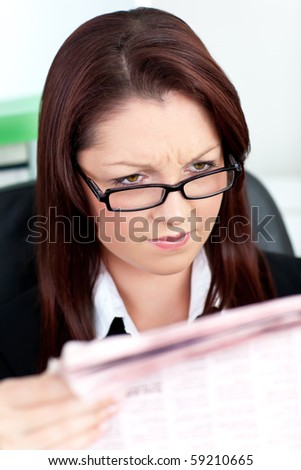 concentrated young businesswoman reading a newspaper in her office - stock photo