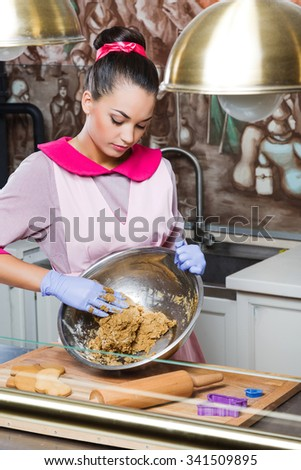 Concentrated young confectioner, wearing in pink dress, apron and violet gloves, kneads the dough in metallic bowl, on wooden board with rolling pin and gingerbread, in the kitchen with painted walls