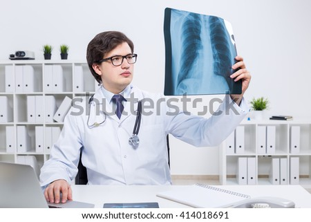 Concentrated young doctor sitting at his office desk and analyzing an x-ray - stock photo