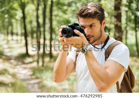 Concentrated young man photographer taking pictures with modern photo camera in forest