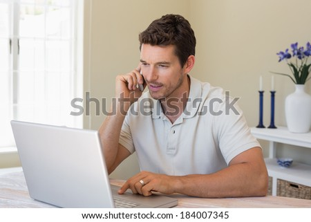 Concentrated young man using laptop and mobile phone at home - stock photo