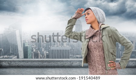 Concentrated young model in winter clothes watching around her against balcony overlooking city