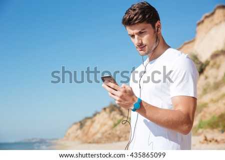 Concentrated young sportsman using smartphone and listening to music on the beach - stock photo