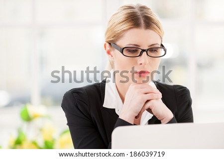 Concentrating at work. Serious mature woman in formalwear holding hands on chin and looking at laptop while sitting at her working place - stock photo
