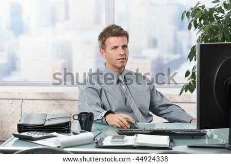 Concentrating businessman working on computer in office - stock photo