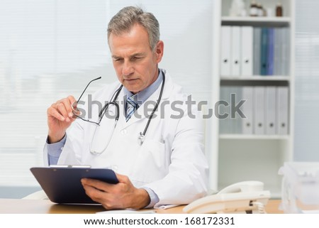 Concentrating doctor sitting at his desk with clipboard in his office at the hospital
