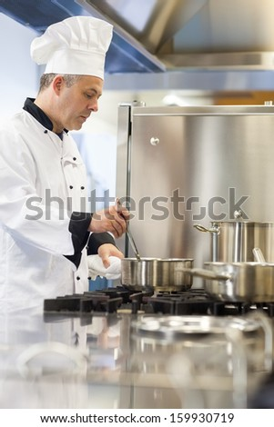 Concentrating head chef stirring in pot in professional kitchen - stock photo
