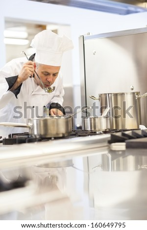 Concentrating head chef tasting food from ladle in professional kitchen - stock photo