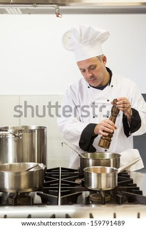 Concentrating head chef using pepper mill in professional kitchen - stock photo