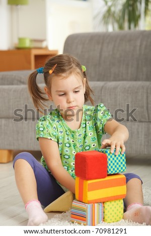 Concentrating little girl (3-4 years) playing with toy blocks at home.? - stock photo