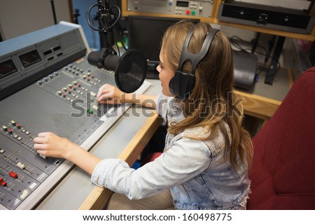 Concentrating pretty radio host moderating sitting in studio at college - stock photo