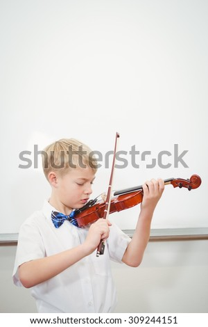 Concentrating Student playing a violin at the elementary school - stock photo