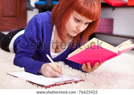 concentrating student write homework on floor in room - stock photo