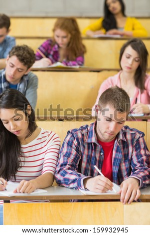Concentrating students sitting at the lecture hall while writing - stock photo