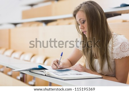 Concentrating woman sitting at the lecture hall while writing out notes - stock photo