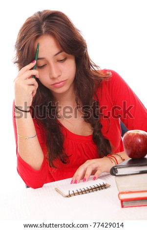 concentration and concern of a beautiful young student with books and an apple on your table - stock photo