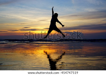 concept about having fun - dramatic sky & reflections silhouette of happy boy jumping over sunset,