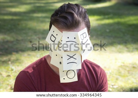 Concept about thoughts and emotions. On the man forehead and face shows (drawn) different icons symbols on yellow stickers. - stock photo
