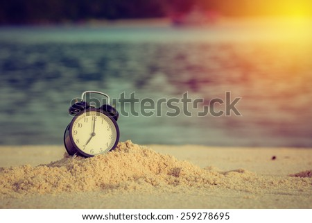 Concept alarm clock on beach of lipe island, thailand. Vintage filter - stock photo
