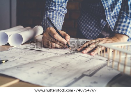 Concept architects,engineer holding pen pointing equipment architects On the desk with a blueprint in the office, Vintage, Sunset light.Selective Focus