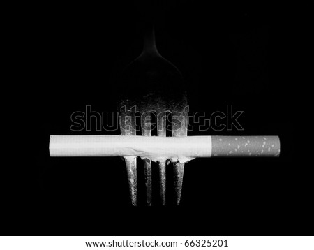 Concept Black white cigarette and fork isolated on black background