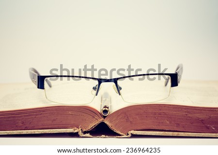 Concept book and eyeglass and pencil. Vintage filter - stock photo