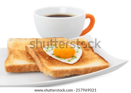 Concept breakfast - slices of wholewheat toast with egg in the shape of heart with coffee - stock photo