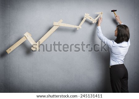 Concept: Building your own successful career or business. Confident businesswoman with hammer in hand building  business graph with positive trend, isolated on grey background. - stock photo