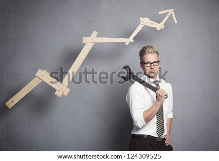 Concept: Building your own successful career or business. Smiling confident businessman holding  wrench in front of business graph with positive trend, isolated on grey background. - stock photo