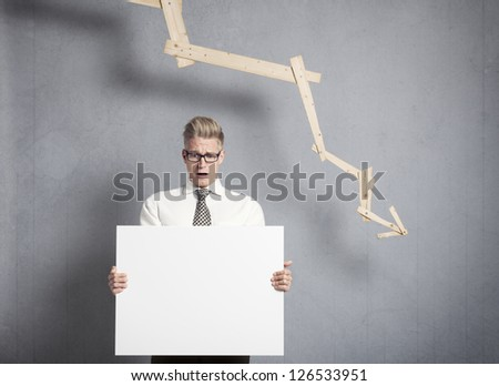 Concept: Business crisis. Worried businessman holding white empty signboard with space for text in front of business graph with negative trend, isolated on grey background. - stock photo