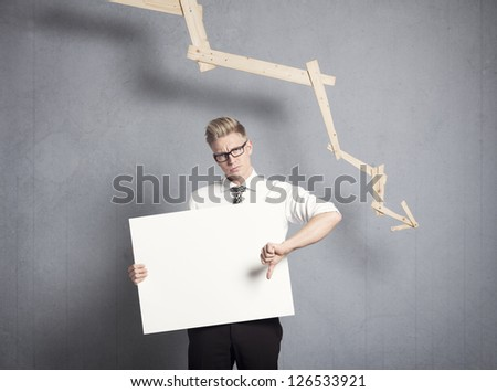 Concept: Business decline. Displeased businessman giving thumbs down at white empty signboard with space for text in front of business graph with negative trend, isolated on grey background. - stock photo