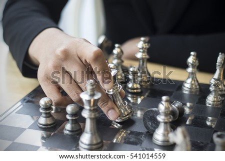 concept businessman thinking about her next move in a game of chess