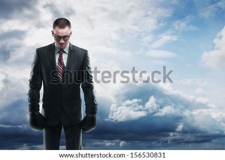 Concept businessman with boxing gloves and shadow standing on sky with clouds