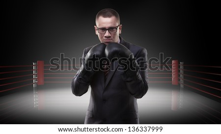Concept businessman with boxing gloves standing on boxing ring - stock photo