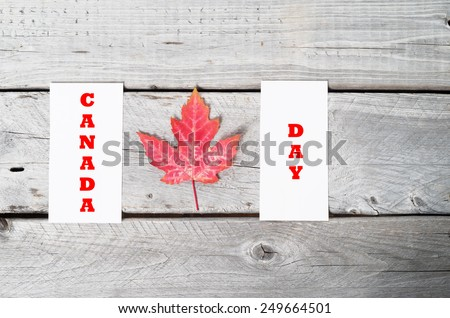 Concept Canada Day with red maple leaf on vintage wooden table - stock photo