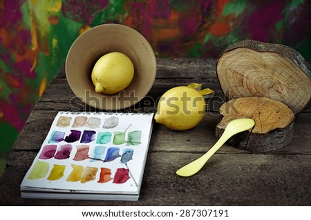 concept composition of paints and notepad and yellow things  on the dark wooden table with painting on the background - stock photo
