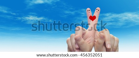 Concept conceptual human or female hands with two fingers painted with a red heart and smiley faces over cloud blue sky background banner for valentine, romantic, love, couple, young, family wedding - stock photo