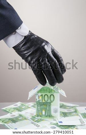 Concept - corruption, theft. Hand in glove leathern designed to steal money. - stock photo