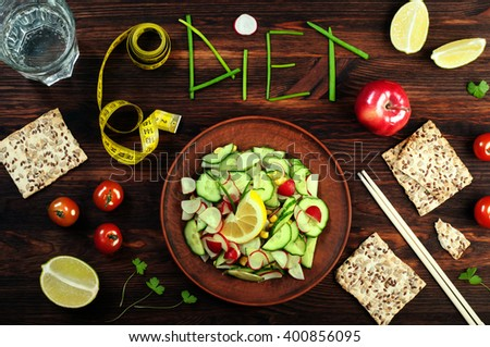 "Concept diet food. Spring menu. Salad with radishes and cucumbers in a brown earthenware dish beside fresh juicy vegetables. The word ""diet"", inlaid of green onions. Brown wood background. - stock photo"