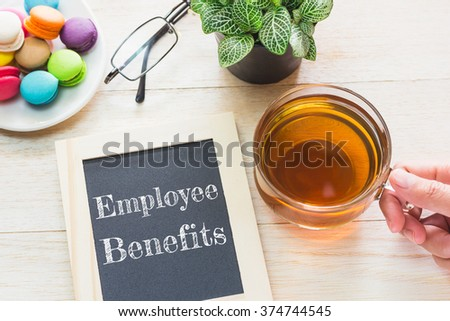 Concept Employee Benefits message on wood boards. Macaroons and glass Tea on table. Vintage tone. - stock photo