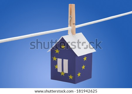 concept - European Union flag painted on a paper house hanging on a rope - stock photo