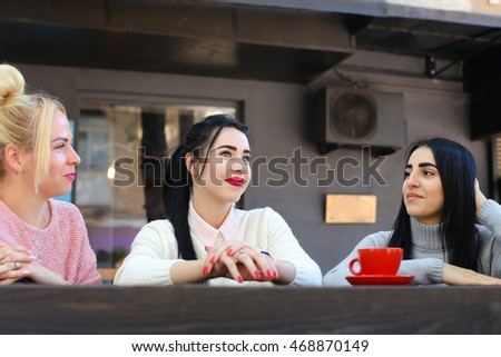 Concept female friendship, meeting, lunch. Three beautiful women sitting incafe smiling, talking, telling secrets, drink coffee