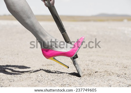 Concept filtered image of female leg in pink high heel stiletto shoe and one hand on shovel, digging in remote sandy desert hole in the dirt, blurred background and copy space. - stock photo