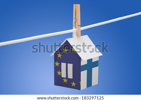 concept - finland and European Union flag painted on a paper house hanging on a rope - stock photo